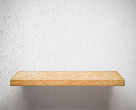 Wooden shelf on white wall photo
