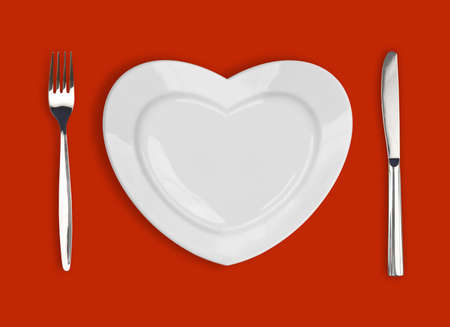 plate setting: plate in shape of heart, table knife and fork on red background Stock Photo