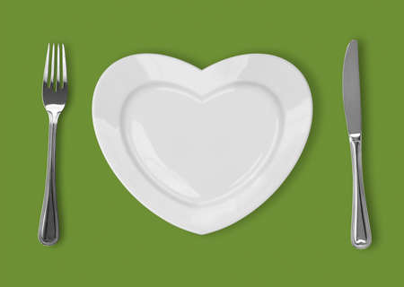 plate in shape of heart, table knife and fork on green background photo