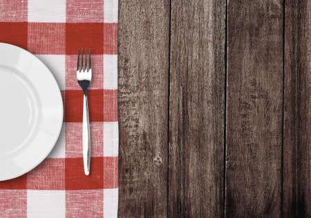 manteles: plato blanco y un tenedor en la mesa de madera vieja con mantel rojo comprobado y copyspace