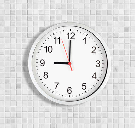 Simple clock or watch on white tile wall displaying nine oclock photo