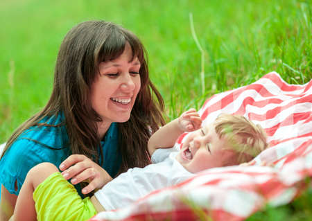 kidding: happy mother and daughter have picnic outdoor on green grass