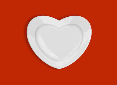 heart shape plate on red background photo