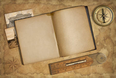 Open diary over old treasure map with compass photo