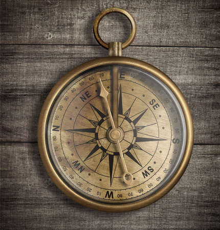 old compass: old brass compass on wood table top view Stock Photo