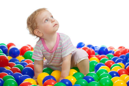 Cute kid or child playing colorful balls looking up photo