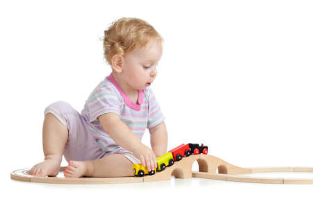beautiful little boys: Cute child is playing with wooden train isolated on white