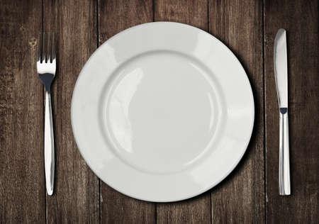 plato de comida: placa blanca, cuchillo y tenedor en la mesa de madera vieja