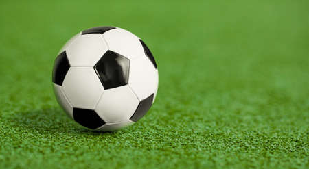 Soccer ball on green grass playground photo