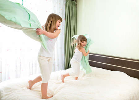 pillow fight: Little girls fighting using pillows in bedroom Stock Photo