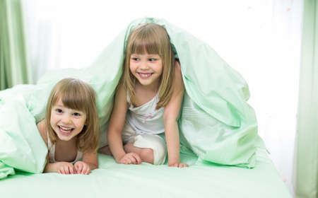 Two little girls lying under blanket on bed photo