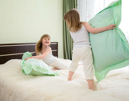 pillow fight: two girls playing with pillows in bedroom