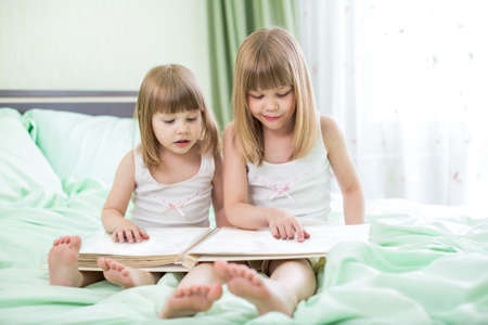 Two little girls reading book sitting on bed photo