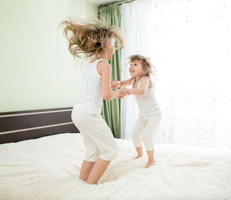 Le bambine saltando sul letto