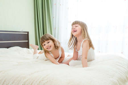 Two little girls lying on bed photo
