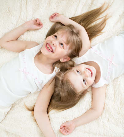 happy kids lying on back in pajamas top view photo
