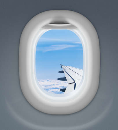 sidelight: airplane window with wing and cloudy sky behind