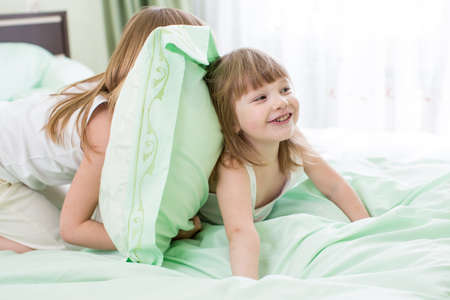 two girls playing in bed photo