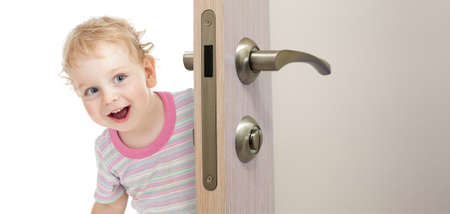hide and seek: happy kid behind door