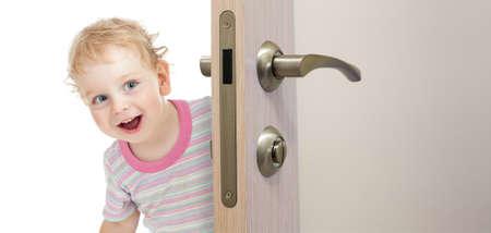 abriendo puerta: niño feliz detrás de la puerta Foto de archivo