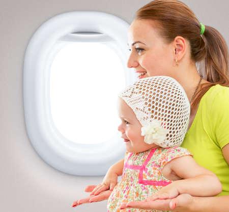 persona viajando: Feliz madre e hijo sentados juntos en cabina del avi�n cerca de la ventana