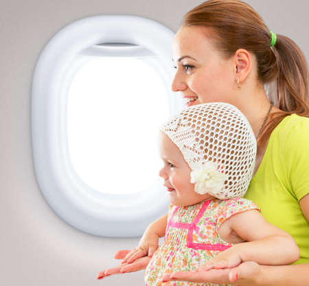 Happy mother and child sitting together in airplane cabin near window photo