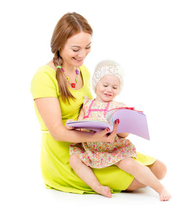 mother and little girl sitting and reading book together isolated on white photo
