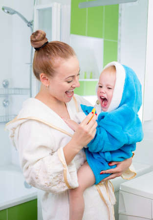 tooth cleaning: Happy mother and child teeth brushing and tongue cleaning performing Stock Photo