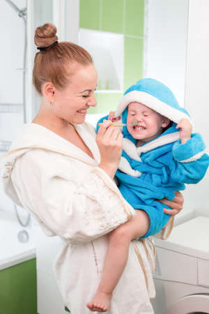 Happy mother and child teeth brushing together in bathroom photo