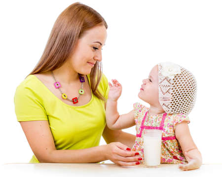 mother milk: mother giving milk glass to little girl sitting at table isolated on white
