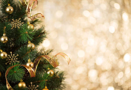 christmas tree design: Gold Christmas background of defocused lights with decorated tree