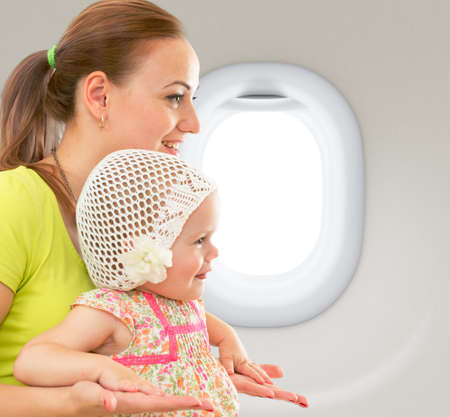travelling: Happy mother and child sitting together in airplane cabin near window