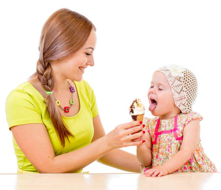 mother giving ice cream to little girl sitting at table isolated on white photo