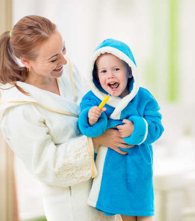 mother and child brushing teeth together in bathroom. Dental hygiene. Stock Photo - 20679642