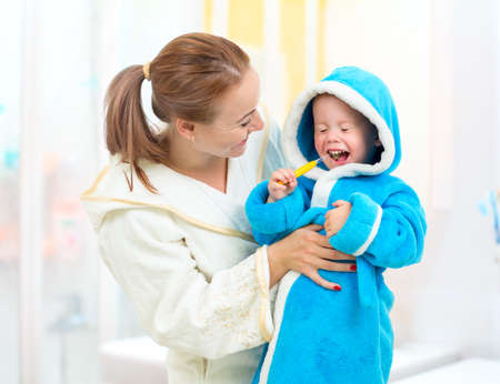 Dental hygiene in bathroom. Mother and child cleaning teeth together. photo