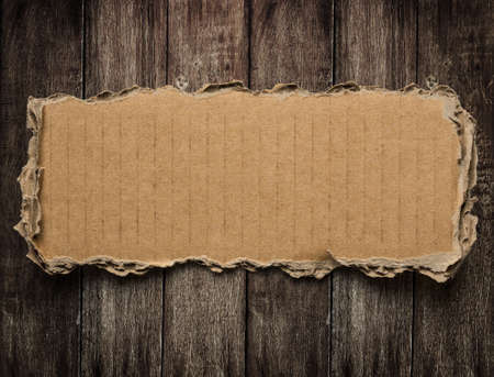 Torn cardboard on wood background photo