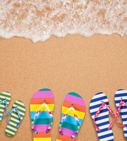 Familys flip flop pairs on sea surf with copy space for your text photo