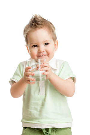 Funny kid drinking water from glass on white photo