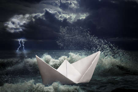 business survival: paper ship in storm concept