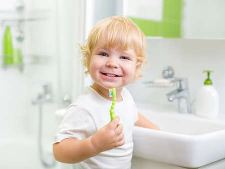 tooth cleaning: Happy kid or child  brushing teeth in bathroom. Dental hygiene.