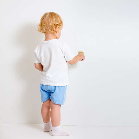 Baby boy with paint brush rear view standing near blank white wall photo