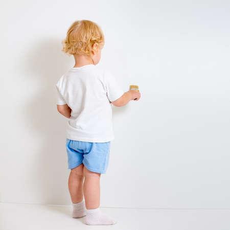 ni�os rubios: Beb� con el cepillo de pintura de visi�n trasera de pie cerca de la pared blanca en blanco