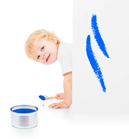 Baby boy with paint brush on all fours behind painted white wall photo