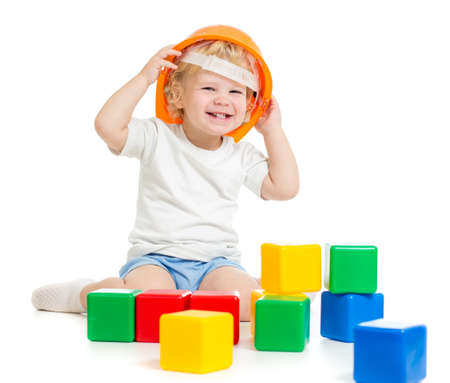 happy kid boy in hard hat playing with colorful building blocks isolated on white Stock Photo - 22217263