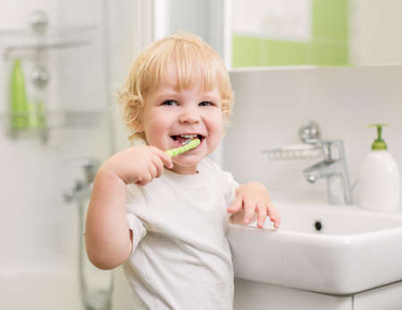 Happy kid brushing teeth photo