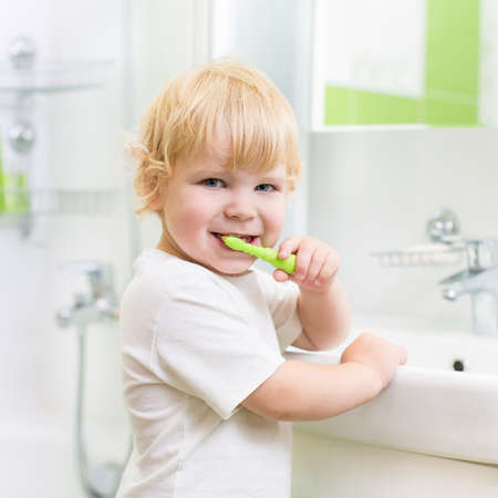 Kid boy brushing teeth in bathroom Stock Photo - 22400765