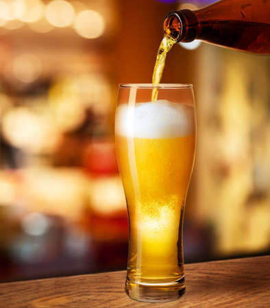 pouring beer in glass on bar or pub desk photo