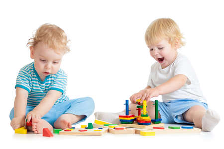 logical: Concentrated child playing logical education toys with great interest on white background