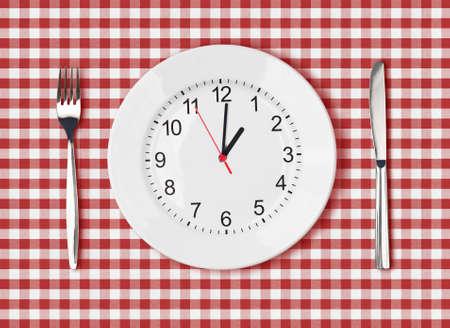 時計の文字盤と赤いピクニック テーブル クロスにフォークとナイフ、ホワイト プレート 写真素材