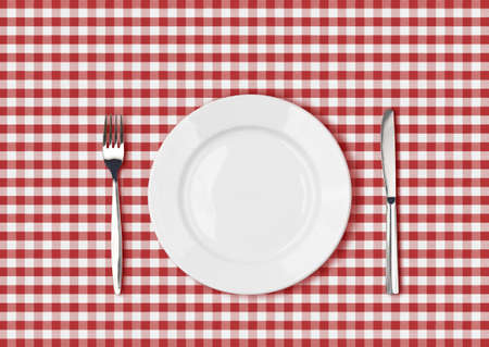 Knife, white plate and fork on red picnic table cloth photo